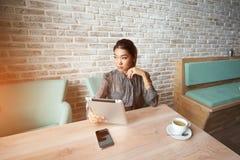 在触摸板的现代女性观看的时尚新闻,当等待在咖啡馆时的命令 图库摄影