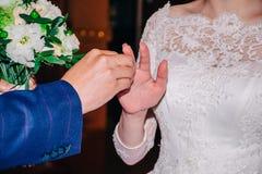 在誓愿的表现期间,新郎投入新娘的手指订婚金戒指 免版税图库摄影