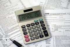 在计算器和报税表的4月15日文本 免版税库存照片
