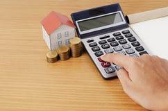 在计算器的手有硬币堆的和抵押的纸房子 免版税库存照片