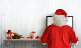 在计算机上的圣诞老人工作在他的屋子里 在墙壁上的自由空间文本的 免版税库存照片