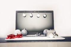 在计算机上的圣诞节装饰 在木桌和白色墙壁上的膝上型计算机 在一个假日期间,企业概念 Xmas概念 库存照片