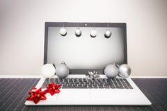 在计算机上的圣诞节装饰 在木桌和白色墙壁上的膝上型计算机 在一个假日期间,企业概念 Xmas概念 库存图片