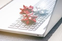 在计算机上的圣诞节装饰 在木桌和白色墙壁上的膝上型计算机 在一个假日期间,企业概念 Xmas概念 免版税库存照片