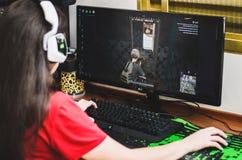 在计算机前面安装的游戏玩家女孩演奏PUBG 免版税库存照片