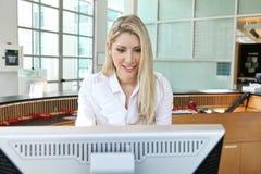 在计算机前面的一个美丽的助理 免版税库存照片