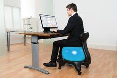 在计算机前面的商人坐普拉提球 库存图片