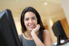在计算机前面的微笑的办公室工作者 图库摄影