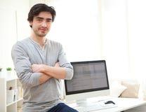 在计算机前面的年轻人 免版税库存图片