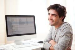 在计算机前面的年轻微笑的人 图库摄影