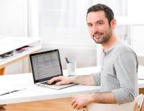 在计算机前面的年轻微笑的人 免版税库存图片