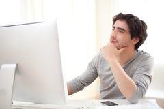 在计算机前面的年轻沉思人 库存照片