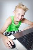 在计算机后的少年 免版税库存照片