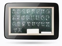 在计算机片剂里面的黑板有概略字母表的 免版税库存照片