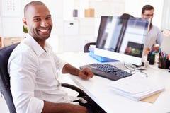 在计算机的商人在办公室开始事务 免版税库存图片