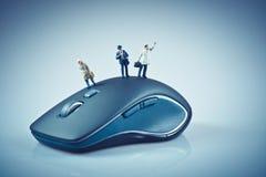 在计算机老鼠顶部的微型人 到达天空的企业概念金黄回归键所有权 库存图片