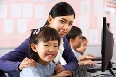 在计算机选件类期间的教师帮助的学员 免版税图库摄影