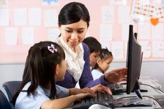 在计算机选件类期间的教师帮助的学员 库存图片
