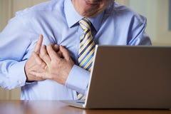 在计算机遭受的心脏病发作的商人 图库摄影