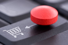 在计算机键盘的红色药片和购物车 免版税图库摄影