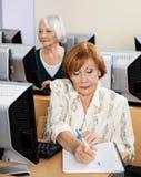 在计算机类的资深妇女文字笔记 免版税库存图片