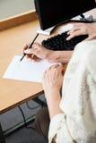 在计算机类的资深妇女文字笔记 库存照片