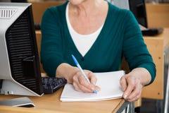 在计算机类的资深妇女文字笔记 免版税图库摄影