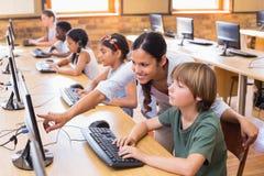 在计算机类的逗人喜爱的学生与老师 库存图片