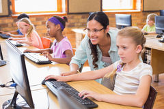 在计算机类的逗人喜爱的学生与老师 免版税库存图片