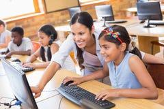 在计算机类的逗人喜爱的学生与老师 库存照片