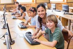 在计算机类的逗人喜爱的学生与老师 图库摄影