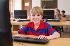 在计算机类的逗人喜爱的学生 免版税库存照片
