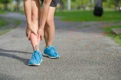 在训练期间,举行他的体育腿伤的健身妇女,干涉痛苦 库存照片