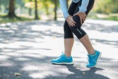 在训练期间,举行他的体育腿伤的年轻健身妇女,干涉痛苦 有亚洲的赛跑者小牛疼痛和问题以后 免版税图库摄影