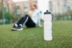 在训练,跑或者体育以后的女孩在前景,一个瓶的休息水 女孩在开放,新鲜空气工作 免版税库存照片