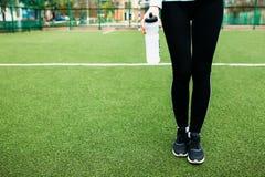 在训练,跑或者体育以后的女孩在前景,一个瓶的休息水 女孩在开放,新鲜空气工作 库存照片