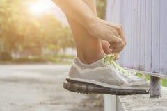 在训练前的女性栓的体育鞋带 库存图片