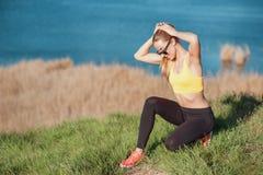在训练期间的一点断裂 美丽的少妇有一阵子坐到放松和在尾巴的梳子头发在exerci前 免版税库存照片