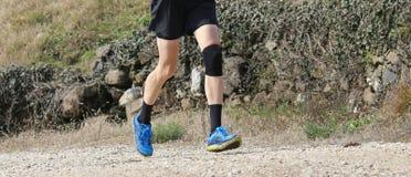 在训练期间的赛跑者与体育服装和护膝垫 免版税库存图片