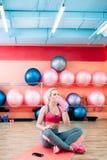 在训练的健身女孩饮用水在健身房 免版税库存照片