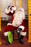 在训练的疲乏的圣诞老人克劳斯断裂在健身房的圣诞节前 免版税库存照片
