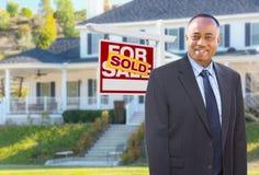 在议院和被卖的标志前面的非裔美国人的代理 免版税库存图片