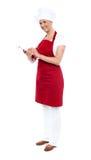 在记事本的俏丽的女性厨师文字食谱 库存图片