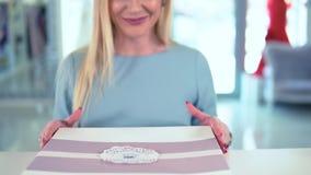 在记数器的愉快的白肤金发的女性得到的被包装的购买项目在豪华精品店 影视素材
