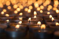在许多火焰状茶光蜡烛中的被点燃的蜡烛 美丽 图库摄影