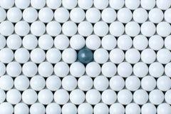 在许多白色部分中的黑电灯泡 airsoft球背景  免版税库存照片