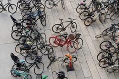 在许多黑自行车中间的一辆红色自行车 免版税库存图片