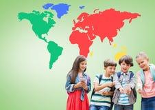 在设备的孩子在五颜六色的世界地图前面 库存图片