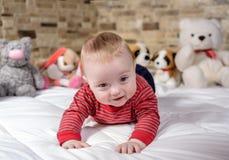 在设法的床上的逗人喜爱的男婴爬行 免版税图库摄影