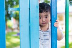 在设法的栅格后的哀伤的亚洲孩子逃脱 浅DOF 库存图片